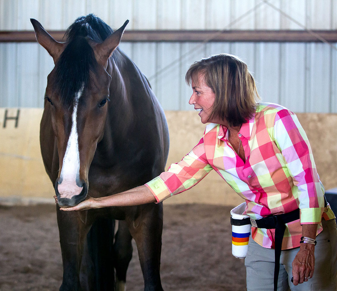 Horse nuzzling Shawna Karrasch's hand in the main barn at Terra Nova Equestrian Training Center in Santa Fe, NM.