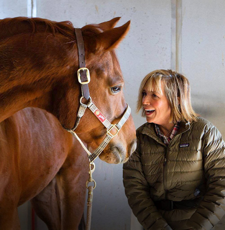 Shawna Karrasch, Positive Reinforcement Trainer and Behaviorist at Terra Nova Equestrian Training Center in Santa Fe, NM with a horse.